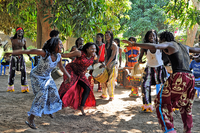 Dancers in colourfull outfits dancing to tthe rhythms of djembe drums, a common sound on a holiday in The Gambia